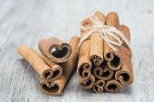 stock photo of condiment  - Cinnamon sticks on an old wooden table background - JPG