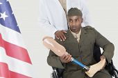 stock photo of military personnel  - Doctor with disabled military officer holding artificial limb as he looks at American flag - JPG
