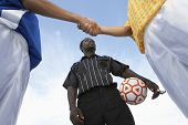stock photo of referee  - Low angle view of referee with opponent team players shaking hand against sky - JPG