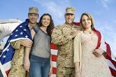 stock photo of united we stand  - Low angle portrait of happy military couples wrapped in American flag against sky - JPG