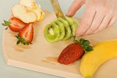 stock photo of cutting board  - Woman cutting fruits on chopping board made from wood - JPG