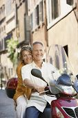 stock photo of scooter  - Happy middle aged couple riding scooter on street in Rome - JPG