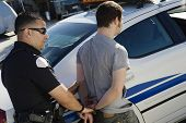 stock photo of handcuffs  - Police Officer Arresting Young Man - JPG