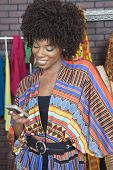 image of palm-reading  - African American female fashion designer reading text message on cell phone - JPG