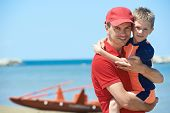 pic of drow  - Lifeguard man with rescued child from drowning on a sea beach - JPG