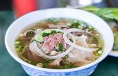 image of brisket  - Bowl of Vietnamese pho noodle soup with rare beef tendon tripe and brisket served with onions and cilantro - JPG