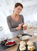 stock photo of cream puff  - Woman in kitchen preparing cream puffs - JPG