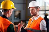 stock photo of warehouse  - Two warehouse workers discussing a new project