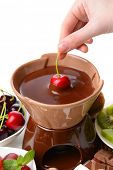 Chocolate fondue with sliced fruits, isolated on white