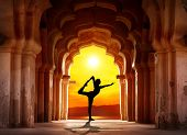 stock photo of natarajasana  - Man silhouette doing yoga in old temple at orange sunset sky background - JPG