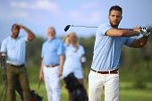 stock photo of swing  - Handsome male golfer swinging golf club - JPG