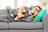 stock photo of pajamas  - Young man in pajamas sleeping on sofa at home with teddy bear - JPG