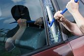 image of hooligan  - Robber with crowbar smashing the glass horizontal - JPG