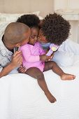 foto of babygro  - Happy parents and baby girl sitting on bed together at home in the bedroom - JPG