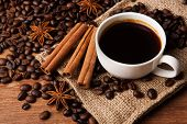 pic of cinnamon sticks  - roasted coffee with cup of black coffee and cinnamon sticks closeup - JPG