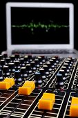 stock photo of potentiometer  - Analog studio music mixer closeup with laptop and sound wave form in nthe background - JPG