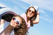 stock photo of car-window  - young attractive woman in sunglasses got out of the car window and laugh  - JPG