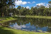 pic of ponds  - Water retention pond near woods and bridge with partly cloudy sky - JPG