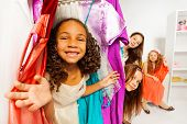 pic of clothes hanger  - Diversity of girls during shopping choosing clothes while standing among hangers with colorful bright dresses and children clothes in the store - JPG