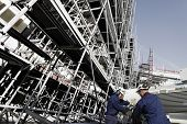 picture of machinery  - building workers with machinery inside large scaffolded site - JPG