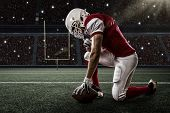 pic of football helmet  - Football Player with a red uniform on his knees on a Stadium - JPG