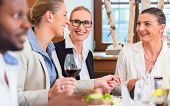 stock photo of lunch  - Group of men and women at business lunch in restaurant eating and drinking - JPG