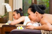 stock photo of oil well  - Two Indonesian Asian women in wellness beauty spa having aroma therapy massage with essential oil - JPG