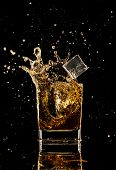 picture of whiskey  - Isolated shot of whiskey with splash on black background - JPG