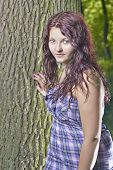 stock photo of wench  - Young girl standing near a tree trunk - JPG