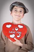 pic of newsboy  - Cute young boy with newsboy cap holding a plush red heart with I love you message on Valentine - JPG