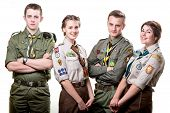 stock photo of boy scouts  - Four young scouts members in uniform on white background - JPG