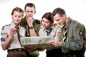 picture of boy scouts  - Four young scout members in uniform looking to the map and compass isolated on white background - JPG