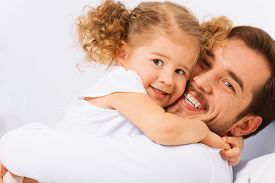 foto of laying-in-bed  - Charming portrait of smiling father and his cute daughter in a hug on the bed in the morning - JPG