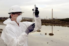stock photo of groundwater  - Worker in a protective suit examining pollution in the water at the industry - JPG