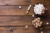 picture of sugar cube  - White and brown sugar cubes in bowl on dark wooden background - JPG