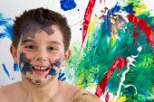 stock photo of face painting  - Happy creative little boy with paint splodges on his face standing in front of his bright colorful modern abstract painting grinning at the camera - JPG