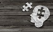 stock photo of wood pieces  - Mental health symbol Puzzle and head brain concept as a human face profile made from crumpled white paper with a jigsaw piece cut out on a rustic old double page spread horizontal wood background - JPG