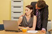 pic of flirt  - Businessman flirting with businesswoman in office - JPG