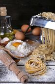 picture of pasta  - Metal pasta maker machine and ingredients for pasta on wooden background - JPG