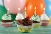 pic of cupcakes  - Delicious birthday cupcakes on table on bright background - JPG