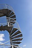 foto of spiral staircase  - Spiral staircase on a roof blue sky background - JPG