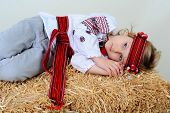 stock photo of manger  - Ukrainian girl in national dress and jeans lying in the manger - JPG