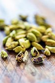 picture of cardamom  - Little green cardamom seeds on the old wooden table - JPG