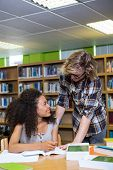 image of classmates  - Student getting help from classmate in library at the university - JPG