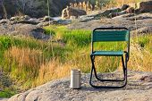 stock photo of lawn chair  - Camp chair and thermos cup on nature background - JPG