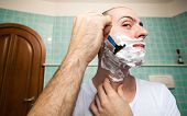 picture of razor  - Man using a disposable razor to shave his beard off  - JPG