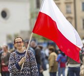 picture of polonia  - Young woman on the street holding a Polish flag - JPG