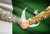stock photo of pakistani flag  - Soldiers shaking hands with flag on background  - JPG