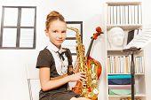 image of saxophones  - Cute girl in school uniform dress holding alto saxophone to play in musical school - JPG