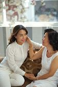 image of grown up  - Beautiful young Vietnamese woman and her grown up daughter talking at home - JPG